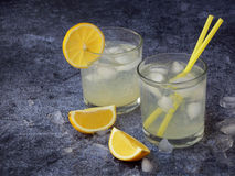 Vidrios de limonada hecha en casa fría con las rebanadas del limón, los cubos de hielo y la paja en fondo oscuro Copie el espacio Fotos de archivo libres de regalías