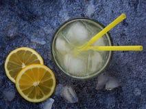 Vidrios de limonada hecha en casa fría con las rebanadas del limón, los cubos de hielo y la paja en fondo oscuro Copie el espacio Foto de archivo