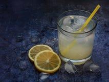 Vidrios de limonada hecha en casa fría con las rebanadas del limón, los cubos de hielo y la paja en fondo oscuro Copie el espacio Foto de archivo libre de regalías