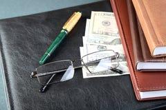 Vidrios de los organizadores de la carpeta una pluma y un dinero Fotos de archivo