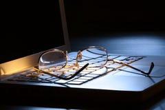 Vidrios de oro en la computadora portátil en luz de luna. Sc oscuro Imagen de archivo