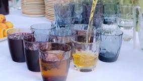 Vidrios de Pouring Juice Into A del camarero en un banquete almacen de metraje de vídeo