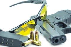 Vidrios de sol anaranjados y pistola negra del arma de 9m m aislada en el fondo blanco Imagenes de archivo