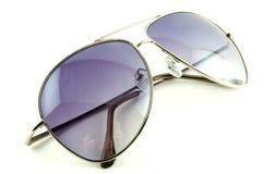 Vidrios de sol de moda púrpuras en un fondo blanco Fotos de archivo