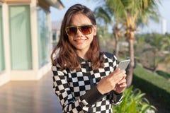 Vidrios de sol de la mujer que llevan asiática joven y teléfono elegante a disposición a Fotos de archivo