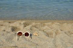 Vidrios de Sun con la estrella de mar en una playa Fotografía de archivo libre de regalías