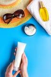 Vidrios de Sun, crema del protiction, sombrero, toalla para la opinión superior del fondo azul del resto de la playa Foto de archivo libre de regalías
