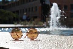 Vidrios de Sun delante de la fuente de agua fotografía de archivo libre de regalías
