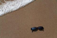 Vidrios de Sun en la arena en la playa Imágenes de archivo libres de regalías