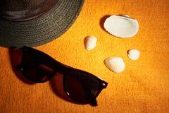 Vidrios de Sun, sombrero rayado y cáscaras del mar foto de archivo