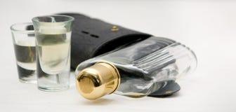 Vidrios de tiro con el frasco y la caja del alcohol del whisky Imagenes de archivo