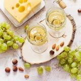 Vidrios de vino blanco, de uvas y de queso en el fondo blanco Fotografía de archivo libre de regalías