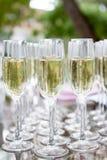 Vidrios de vino blanco del champán Vidrios de cristal con las bebidas coloreadas en la tabla Foto de archivo