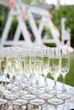 Vidrios de vino blanco del champán Vidrios de cristal con las bebidas coloreadas en la tabla Foto de archivo libre de regalías