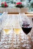 Vidrios de vino blanco del champán, vino rojo Vidrios de cristal con las bebidas coloreadas en la tabla Imagenes de archivo