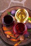 Vidrios de vino blanco del rojo, color de rosa y con la uva en bodega Comida y concepto de las bebidas Fotos de archivo libres de regalías