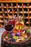 Vidrios de vino blanco del rojo, color de rosa y con la uva en bodega Comida y concepto de las bebidas Imagen de archivo libre de regalías