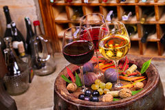 Vidrios de vino blanco del rojo, color de rosa y con la uva en bodega Comida y concepto de las bebidas Foto de archivo