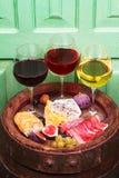 Vidrios de vino blanco del rojo, color de rosa y con la uva, los higos y las nueces en bodega Fotos de archivo