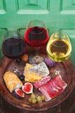 Vidrios de vino blanco del rojo, color de rosa y con la uva, los higos y las nueces en bodega Fotografía de archivo libre de regalías