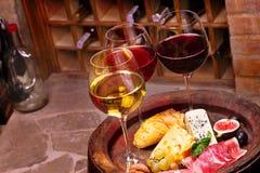 Vidrios de vino blanco del rojo, color de rosa y con la uva, los higos y las nueces en bodega Imagenes de archivo
