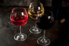 Vidrios de vino blanco rojo, rosado y Fotos de archivo