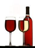 Vidrios de vino blanco rojo y, con la botella de vino rojo Fotografía de archivo