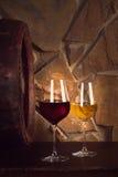 Vidrios de vino blanco rojo y en la bodega, barril de vino viejo Foto de archivo