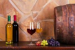 Vidrios de vino blanco rojo y en la bodega, barril de vino viejo Imagen de archivo