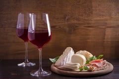 Vidrios de vino con queso, pan, las nueces, el prosciutto y la albahaca Vino y comida en la tabla de madera Imágenes de archivo libres de regalías