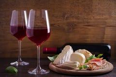 Vidrios de vino con queso, pan, las nueces, el prosciutto y la albahaca Vino y comida en la tabla de madera Foto de archivo