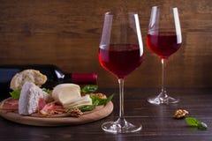 Vidrios de vino con queso, pan, las nueces, el prosciutto y la albahaca Vino y comida en la tabla de madera Fotos de archivo