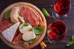 Vidrios de vino con queso, pan, las nueces, el prosciutto y la albahaca Vino y comida en la tabla de madera Fotografía de archivo libre de regalías