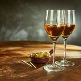 Vidrios de vino en la tabla de madera con las aceitunas verdes Imagen de archivo