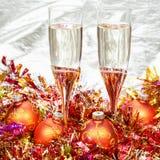 Vidrios de vino espumoso con las chucherías de Navidad del oro Fotografía de archivo