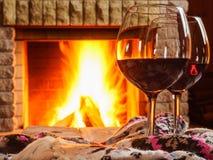 Vidrios de vino rojo con cosas de las lanas, antes de la chimenea acogedora Foto de archivo libre de regalías