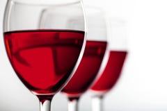 Vidrios de vino rojo en el fondo blanco Imagen de archivo libre de regalías