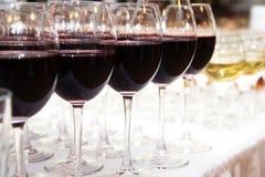 Vidrios de vino rojo en el primer blanco de la tabla Imágenes de archivo libres de regalías