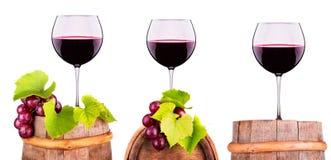 Vidrios de vino rojo en un barril de madera con la uva Fotografía de archivo