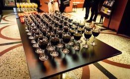 Vidrios de vino rojo en una tabla en un partido Imagen de archivo libre de regalías