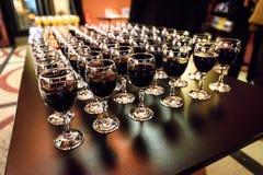 Vidrios de vino rojo en una tabla en un partido Foto de archivo