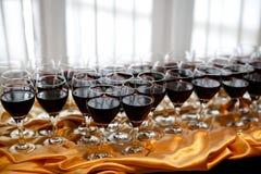 Vidrios de vino rojo en una tabla en un partido Fotos de archivo