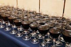 Vidrios de vino rojo en una tabla en un partido Imágenes de archivo libres de regalías