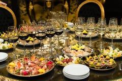 Vidrios de vino rojo y de arrancadores en la tabla del banket fotos de archivo libres de regalías