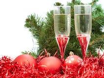 Vidrios de vino y árbol y bolas rojas de la Navidad Foto de archivo libre de regalías