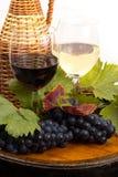 Vidrios de vino y de uvas en barril Imagenes de archivo