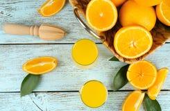 Vidrios de zumo de naranja fresco con la fruta Foto de archivo libre de regalías