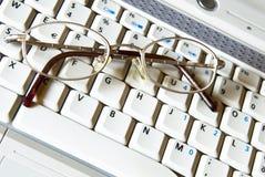 Vidrios del asunto en un teclado de la computadora portátil imagen de archivo libre de regalías
