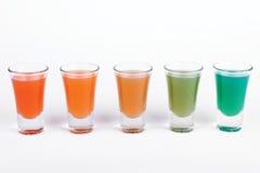 Vidrios del cóctel en diverso color en el fondo blanco Imagen de archivo