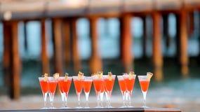Vidrios del cóctel rojo en el partido de la playa Imagen de archivo libre de regalías